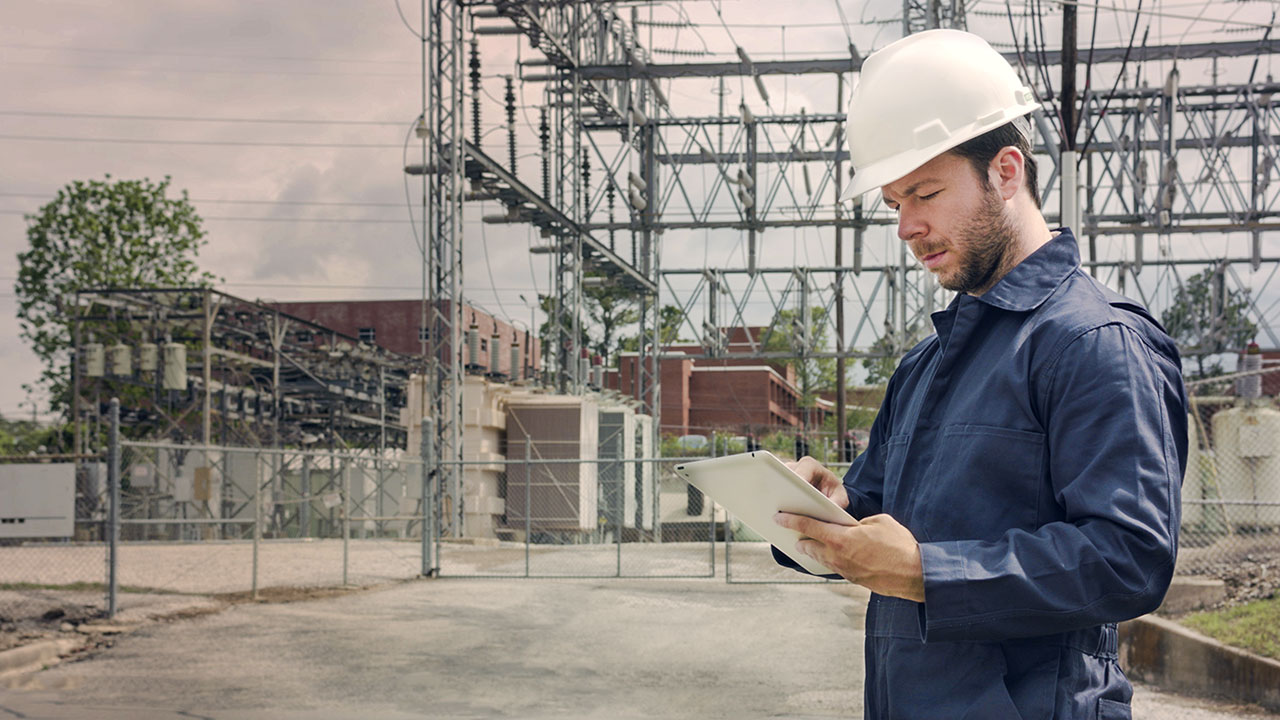 Security technician checking infrastructure details while onsite at a local power grid.