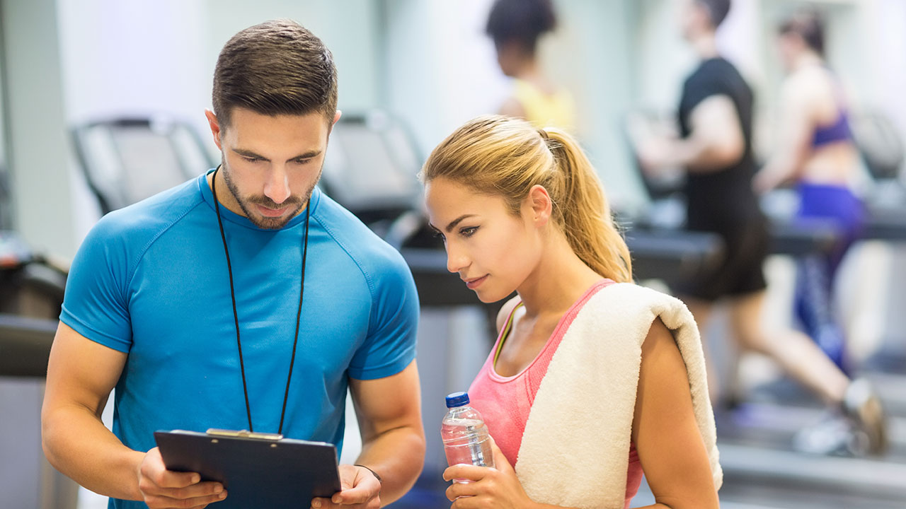 personal trainer talking to woman with clipboard at gym