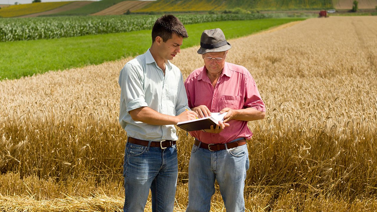 Young man reviewing the crop history of a local farm with the farm's owner.
